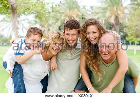 Granparents piggy-ride donnant aux jeunes générations comme ils sourient à huis clos Banque D'Images