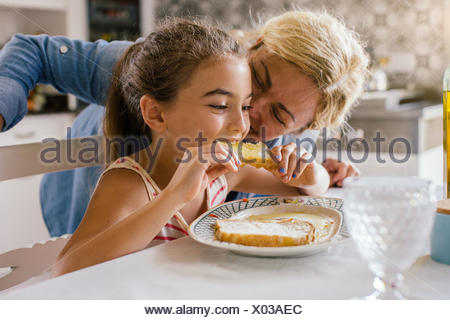 Girl eating toast avec grand-mère Banque D'Images