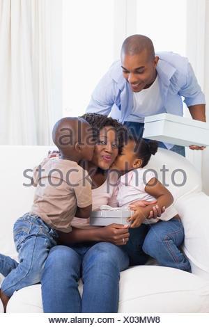 Famille heureuse sur la table mère donnant présente Banque D'Images