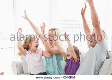 Célébrer la réussite de la famille tout en regardant la télévision Banque D'Images