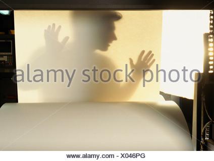 Silhouette d'homme derrière feuille de papier Banque D'Images