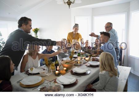La famille et les amis toasting champagne et verres à vin de table au dîner de Thanksgiving Banque D'Images