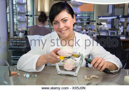 Zahntechnikerin dans un laboratoire dentaire avec des dentiers. Banque D'Images