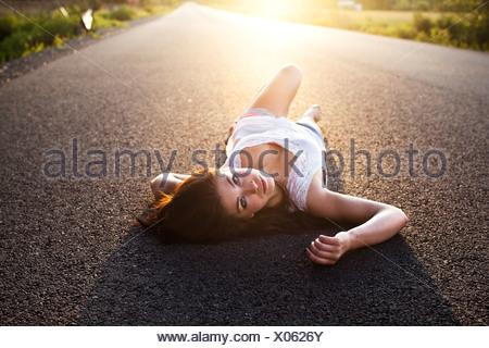 Une fille se trouve sur la route au coucher du soleil dans l'Idaho. Banque D'Images