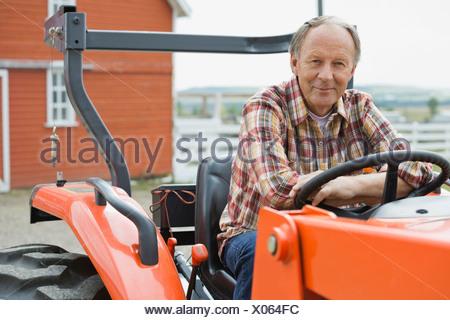 Senior male farmer assis sur le tracteur à la ferme Banque D'Images