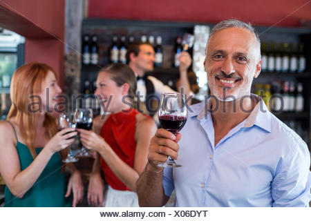 Portrait of smiling man holding glass of red wine
