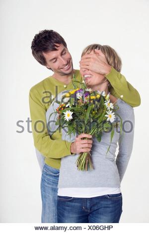 Young man giving woman bouquet de fleurs, portrait Banque D'Images