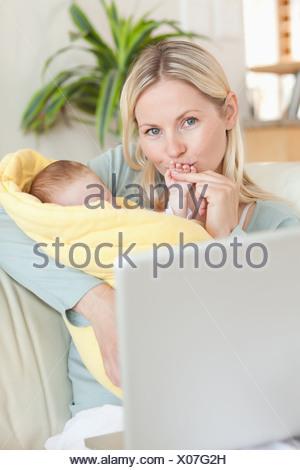 Mère embrassant la main de son bébé tout en étant assis sur le canapé Banque D'Images