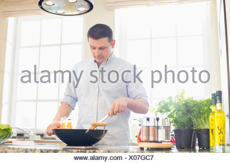 Middle-aged man preparing food in kitchen Banque D'Images