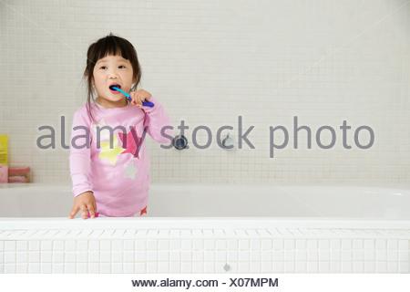 Young Woman standing in baignoire se brosser les dents Banque D'Images