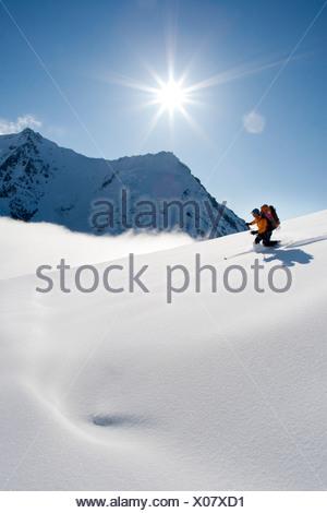La skieuse de l'arrière-pays redescend par poudre et soleil pour la selle entre pic du cratère et le Mont Spurr, montagnes Tordrillo, Alaska Banque D'Images