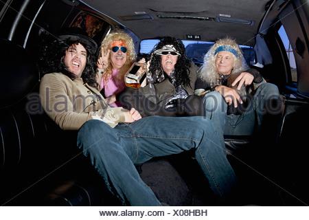 Groupe d'amis profitant de l'alcool en limousine Banque D'Images