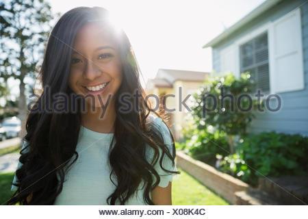 Portrait of teenage girl smiling brunette cour avant ensoleillée Banque D'Images