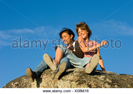 Low angle view of two female friends sur une falaise contre le ciel bleu Banque D'Images