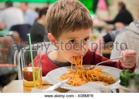 Garçon assis dans un restaurant mange du spaghetti Banque D'Images