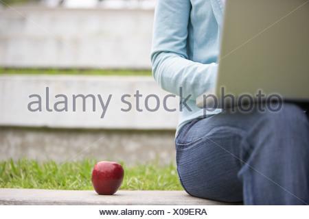 Femme assise sur le mur à côté de l'aide de Red Apple laptop mid section Vue avant, differential focus Banque D'Images