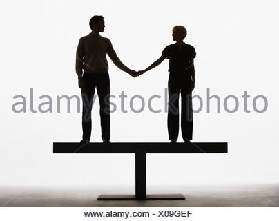 Couple debout sur une planche holding hands Banque D'Images