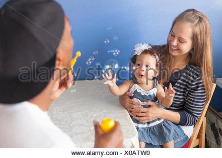 Mère et père jouant avec sa jeune fille, père blowing bubbles Banque D'Images