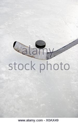 A proximité de la glace en bâton de hockey sur glace en position de frapper rondelle de hockey Banque D'Images