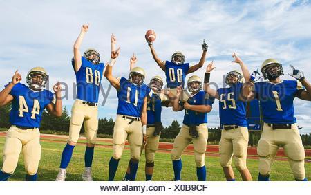 Les adolescentes et les jeunes équipes de football américain célèbre sur terrain de football