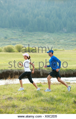 Un couple d'athlétisme course en sentier à travers un champ à côté d'une rivière. Banque D'Images