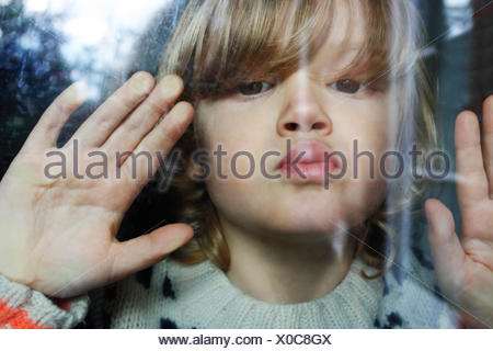 Close-up portrait of boy appuyant sur les lèvres et les mains contre la vitre Banque D'Images