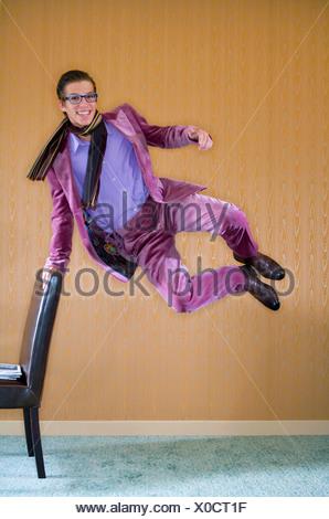 Jeune homme en costume violet saute de joie Banque D'Images