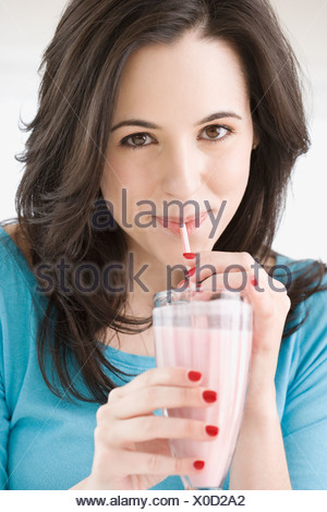 Woman drinking milk-shake avec de la paille Banque D'Images