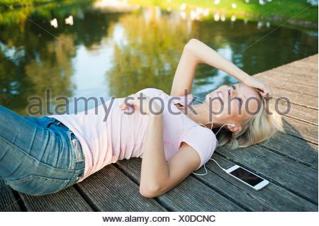 Young woman lying on pier avec mp3 player Banque D'Images