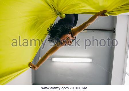 Femme danse aérien en tête en bas à partir d'un tissu de soie Banque D'Images