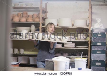 Potter femelle carrying tray de pots d'argile dans l'atelier Banque D'Images