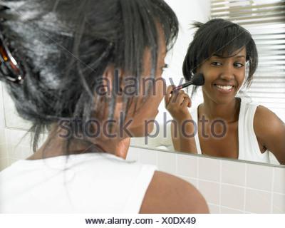 Femme dans la salle de bains, appliquant le maquillage Banque D'Images