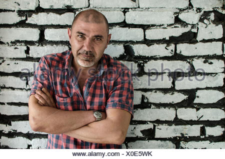 Portrait of a man with arms crossed standing par un mur de briques Banque D'Images