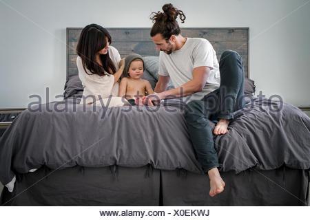 Un jeune couple et leur jeune fils, assis sur leur lit.