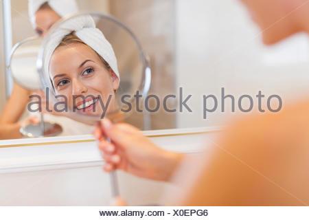 Belle femme à la réflexion elle-même en petit miroir. Debica, Pologne Banque D'Images