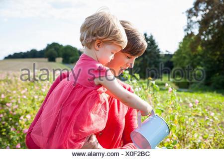 Mid adult mother and toddler fille arrosage des fleurs dans le champ de fleurs Banque D'Images
