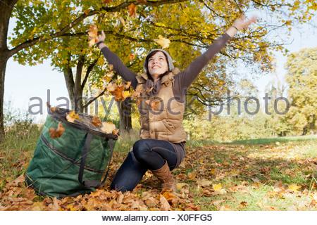 Femme jouant avec les feuilles d'automne dans le parc Banque D'Images