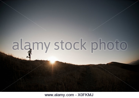 Woman running on dirt path Banque D'Images