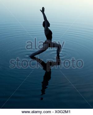 Woman in yoga pose dans le lac Banque D'Images