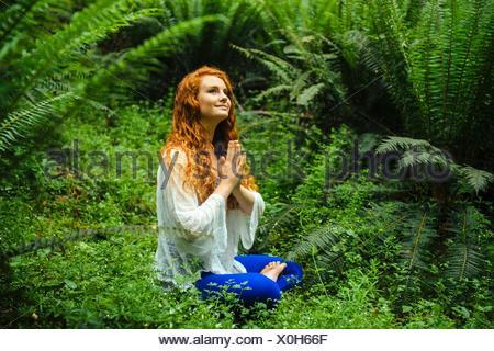 Jeune femme à la pratique du yoga dans la position du lotus Banque D'Images