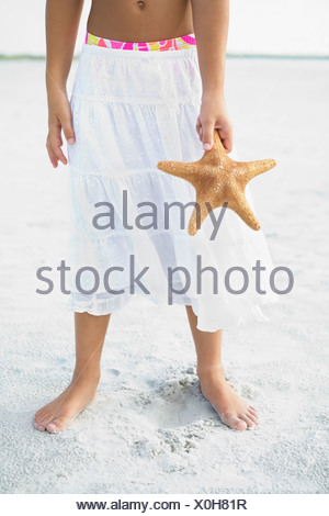 Girl on beach holding starfish Banque D'Images