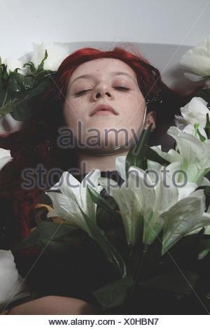 La mode, de l'adolescence immergé dans l'eau avec des roses blanches, scène romantique Banque D'Images