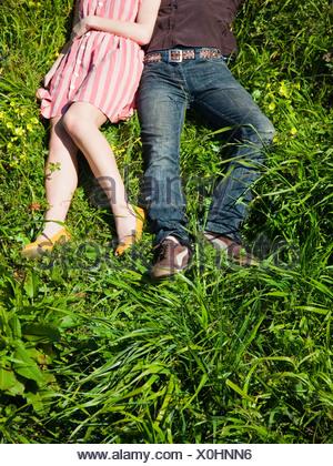 Etats Unis, San Francisco, Californie, young couple lying on grass, low section Banque D'Images