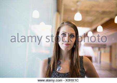 Portrait woman leaning on window Banque D'Images