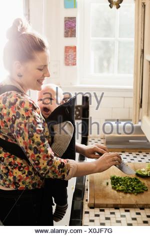 Mère de préparer des aliments adultes milieu avec bébé fils dans sling Banque D'Images