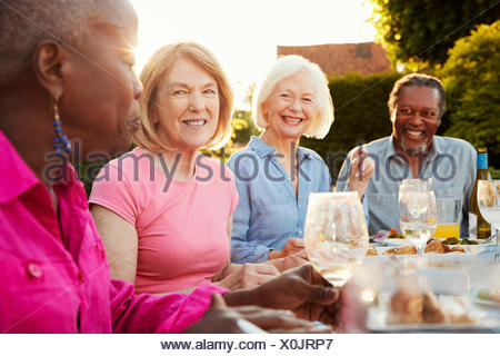 Groupe de hauts friends enjoying outdoor dinner party at home Banque D'Images