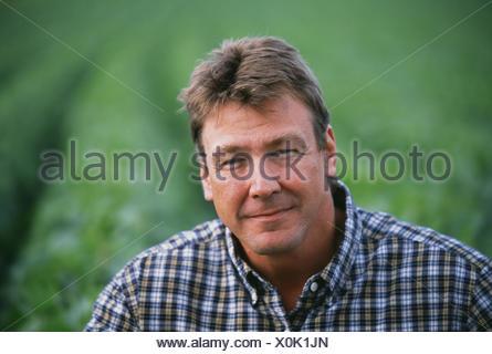 Agriculture - Portrait d'un agriculteur avec son domaine de croissance moyenne dans l'arrière-plan de soja / Minnesota, USA. Banque D'Images