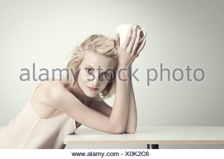 Young woman holding Coffee cup à table, portrait Banque D'Images