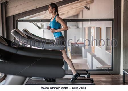 Jeune femme d'exécution sur un tapis roulant Banque D'Images