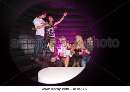 Jeune couple dansant dans une boîte de nuit avec leurs amis, pour avoir un verre Banque D'Images